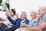 Germany, Leipzig, Senior men and women sitting on coach, smiling - WESTF018782