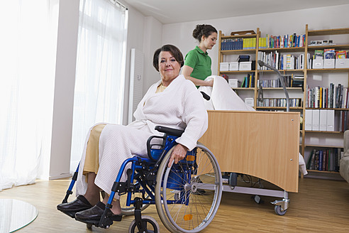 Germany, Leipzig, Senior woman sitting on wheelchair another woman arranging medical bed - WESTF018839
