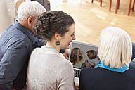 Germany, Leipzig, Man and women watching pictures on laptop - WESTF018863
