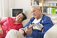Germany, Leipzig, Senior man playing electric guitar on sofa, woman sitting beside - WESTF018881