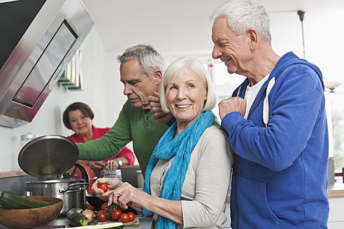 Germany, Leipzig, Senior men and women cooking food - WESTF018893