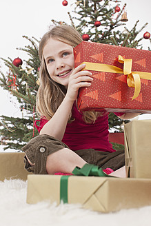 Girl sitting on carpet with gifts, christmas tree in background - BMYF000334