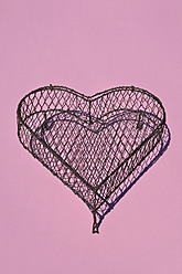 Heart shape cage made by wire on pink background, close up - AXF000092