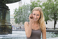 Germany, Bavaria, Munich, Young woman talking on phone in front of Ludwig Maximilian University, smiling - TCF002801