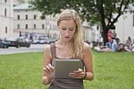 Germany, Bavaria, Munich, Young woman using tablet pc in front of Ludwig Maximilian University - TCF002820