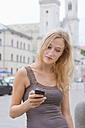 Germany, Bavaria, Munich, Young woman using smart phone in front of Ludwig Maximilian University - TCF002805