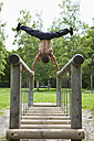 Germany, Bavaria, Young man doing handstand on railing - MAEF004779