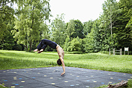 Germany, Bavaria, young man performing somersault - MAEF004783