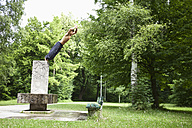 Germany, Bavaria, Young man doing parcour training in park - MAEF004788
