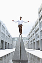Germany, Bavaria, Young businessman standing on top with arm outstretched - MAE004802