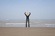 Belgium, Young woman meditating at North Sea - GWF001874