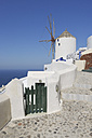Greece, Windmill with cobbled path and green gate in traditionally Greek village Oia at Santorini - RUEF000979