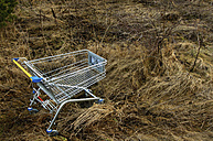 Germany, Bavaria, View of empty shopping trolley in field - AXF000153