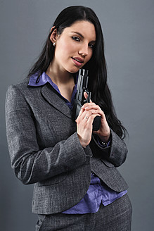Young woman wearing holding gun, portrait, close up - RDF001024