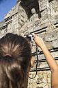 Indonesia, Young woman taking photo of Buddha statue at Borobudur Temple - MBEF000409