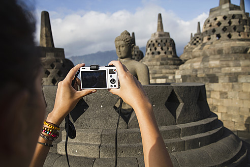 Indonesia, Young woman taking photo of Buddha statue at Borobudur Temple - MBEF000411