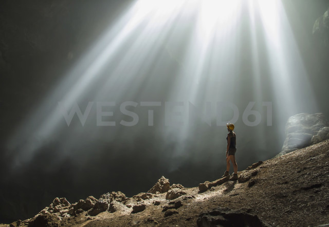 Indonesia, Young woman looking at sunbeam - MBE000418