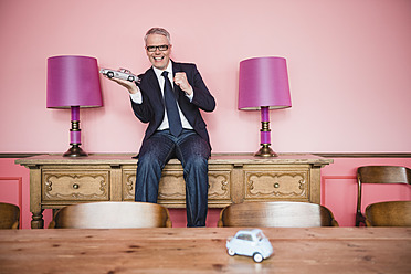 Germany, Stuttgart, Businessman sitting on sideboard with toy car, smiling, portrait - MFP000126