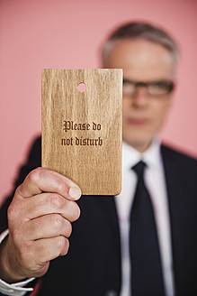 Germany, Stuttgart, Businessman holding do not disturb sign - MFP000129