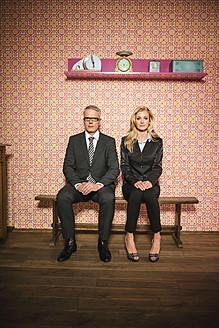 Germany, Stuttgart, Business couple sitting on bench, smiling, portrait - MFP000150