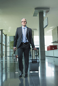 Germany, Stuttgart, Businessman pulling luggage in office building - MFPF000207