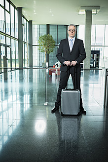 Germany, Stuttgart, Businessman standing with luggage in office building - MFPF000210