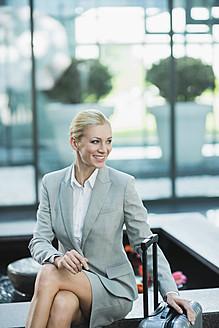 Germany, Stuttgart, Businesswoman sitting with wheeled luggage, smiling - MFPF000216