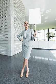 Germany, Stuttgart, Businesswoman standing with blank signs in office lobby, portrait - MFPF000237