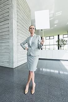 Germany, Stuttgart, Businesswoman standing with blank signs in office lobby, portrait - MFPF000237