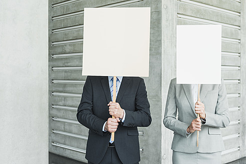 Germany, Stuttgart, Business people holding blank signs in office lobby - MFPF000243