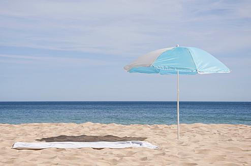 Portugal, Lagos, Beach towel and sunshade on beach - UMF000354