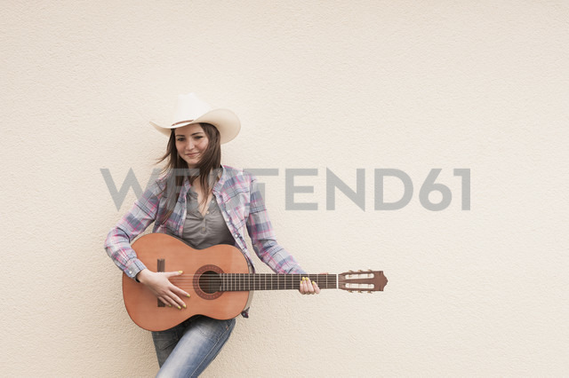 Germany, North Rhine Westphalia, Young woman with cowboy hat playing acoustic guitar, smiling - KJF000163