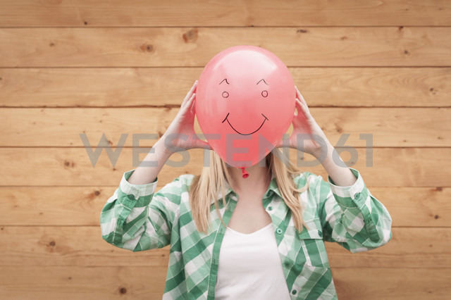 Germany, North Rhine Westphalia, Teenage girl covering face with smiley face balloon - KJF000165