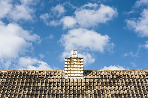 Germany, North Rhine Westphalia, Duesseldorf, View of tiled roof with chimney against clouds - KJF000173