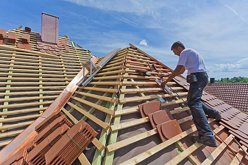Germany, Baden-Wuerttemberg, Stuttgart, Mid adult man measuring roof tile - WDF001253