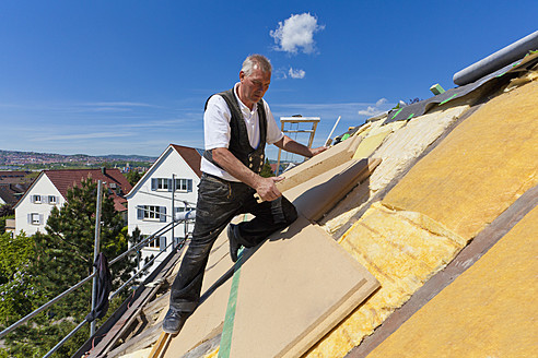 Germany, Baden-Wuerttemberg, Stuttgart, Mature man placing insulation - WDF001270