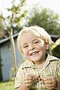 Germany, Bavaria, Boy holding red currants, smiling, portrait - RNF000990
