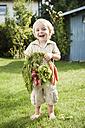 Germany, Bavaria, Boy holding carrots and red radish, smiling, portrait - RNF000992