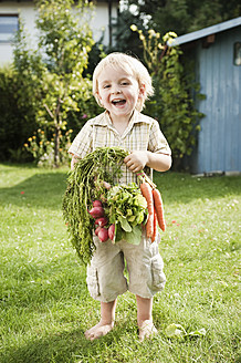 Germany, Bavaria, Boy holding carrots and red radish, smiling, portrait - RNF000992