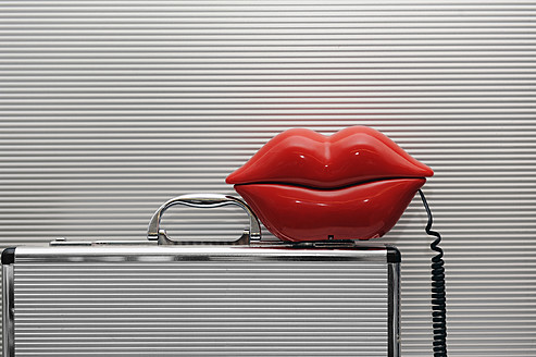 Lip shaped telephone on briefcase, close up - LRF000550