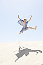 France, Boy jumping on sand dune - MSF002727