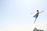 France, Teenage boy jumping on sand dune after football - MSF002751
