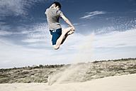 France, Teenage boy jumping on sand dune - MSF002749
