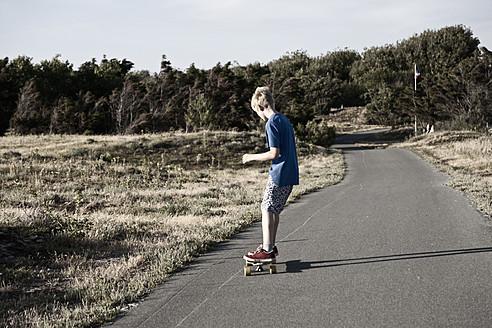 France, Boy longboarding on road - MSF002742