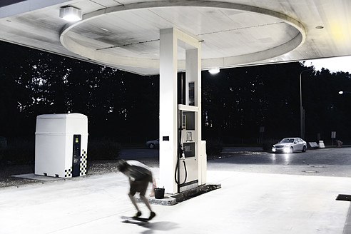 France, Poitiers, Teenage boy skating on petrol station - MSF002740