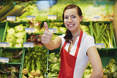 Germany, Cologne, Young woman showing thumbs up in supermarket, smiling, portrait - RKNF000004
