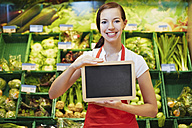 Germany, Cologne, Young woman with blackboard in supermarket, smiling, portrait - RKNF000007