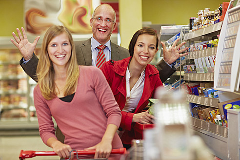 Germany, Cologne, Man and women in supermarket, smiling, portrait - RKNF000034