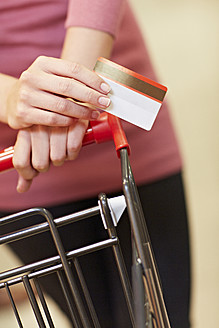 Germany, Cologne, Young woman holding credit card in supermarket - RKNF000037