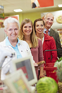 Gemany, Cologne, Man and woman waiting in supermarket, smiling - RKNF000043